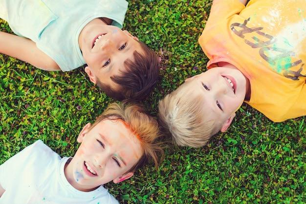 ホーリー祭の色で描かれた子供たち。男の子は緑の芝生に横たわっています。ホーリー祭。ホーリー祭の間に楽しんでいる友達。幸せな子供時代。色で遊んでいる10代前の男の子。 Premium写真