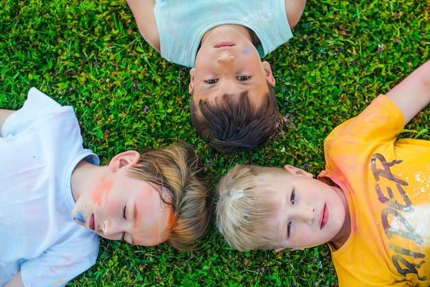 ホーリー祭の色で描かれた子供たち。男の子は緑の芝生に横たわっています。ホーリー祭。
