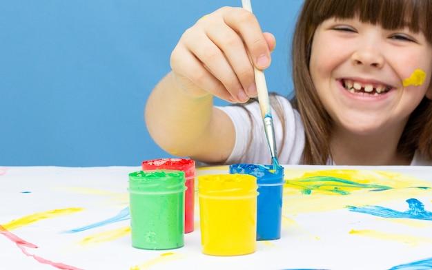 이젤에 붓을 그리는 아이들. 아이 소녀는 집에서 혼자 페인트를 배웁니다. 클래스 학교에서 배경에 아이 그림입니다. 학생들은 그녀가 가장 좋아하는 선생님을 위해 꽃을 그립니다.