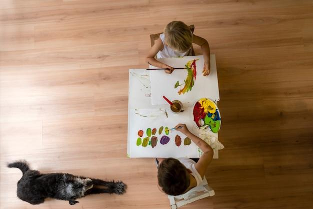 바닥에 누워 강아지와 함께 테이블에 그림을 그리는 아이들