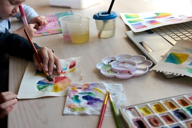 アートレッスン中に水彩絵の具で絵を描く子供たち。生徒たちは筆で描くことに集中しています。水彩カラーホイールとパレット。色彩理論初心者の趣味のレッスン