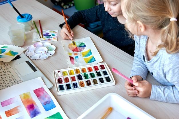 Дети рисуют картины акварельными красками во время урока рисования. ученики концентрируются на рисовании кистью. цветовое колесо и палитра акварели. уроки хобби для начинающих по теории цвета.