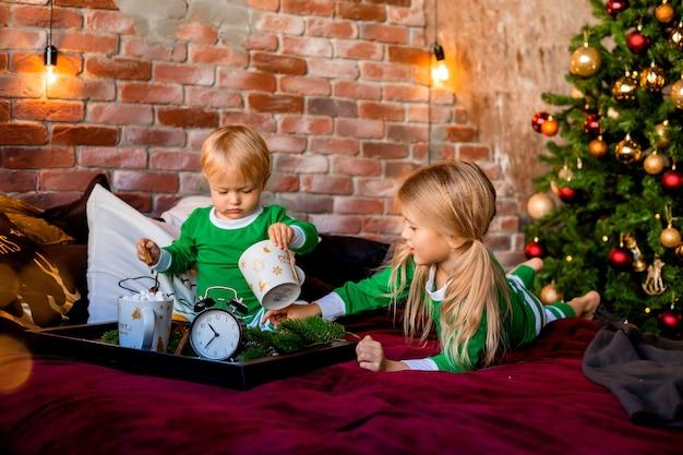Children in pajamas having cocoa near christmas tree