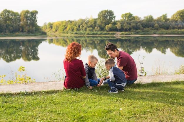 子供、親子関係、自然の概念-草の上に座っている大家族