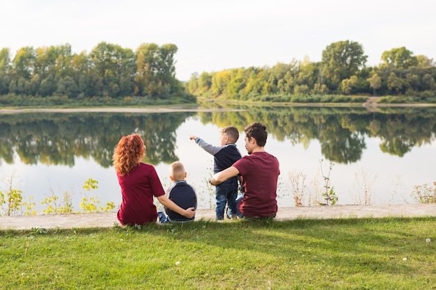 Children, parenthood and nature concept - big family sitting on the grass