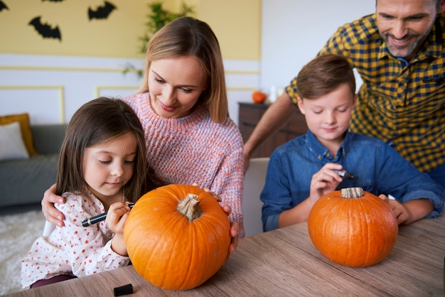 Children and parents drawing on pumpkins