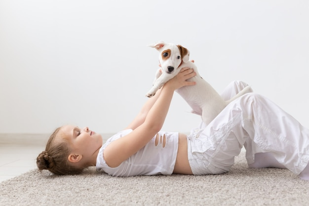 Концепция детей, домашних животных и животных - девочка играет со своим щенком джек-рассел-терьера в помещении