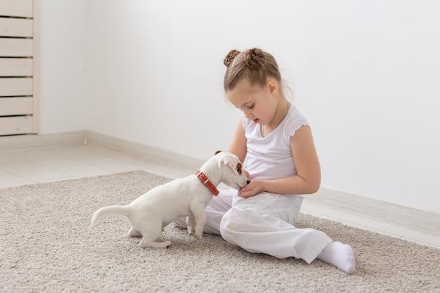 子供、ペット、動物のコンセプト-床でジャックラッセルテリアの子犬と遊ぶパジャマの小さな子供の女の子