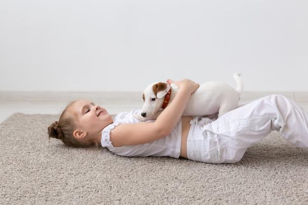 子供、ペット、動物のコンセプト-子犬と一緒に床に横たわっている小さな面白い愛らしい子供の女の子。