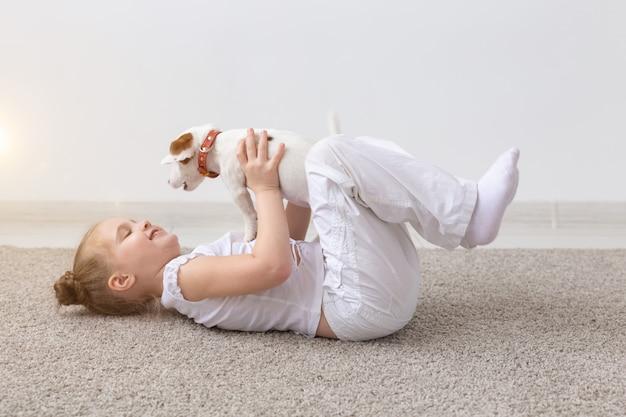 子供、ペット、犬のコンセプト-床に横たわって面白い子犬ジャックラッセルテリアと遊んでいる小さな愛らしい子供の女の子