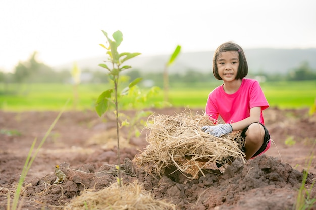 Children planting the tree on land  and blurred nature background
