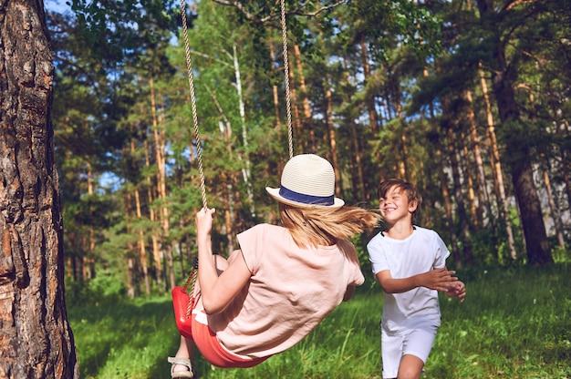子供たちは自然の中で遊んで笑います。少年がブランコに乗って少女を揺さぶる。ライフスタイル写真