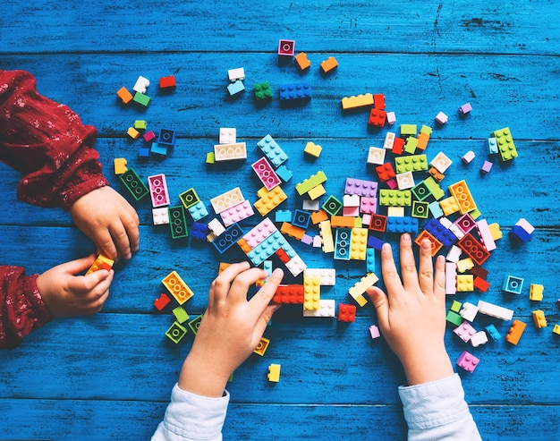 Children play and build with colorful toy bricks or plastic blocks on table