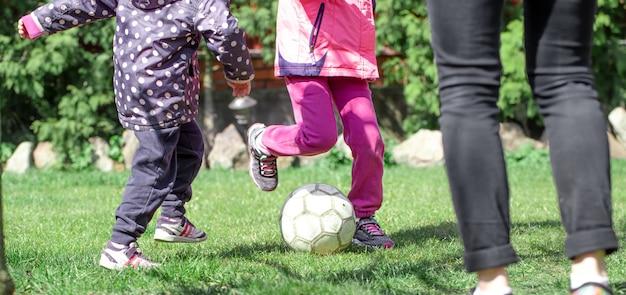 子供たちは芝生でサッカーをし、ボールに足を置きます。チームゲームのコンセプト。