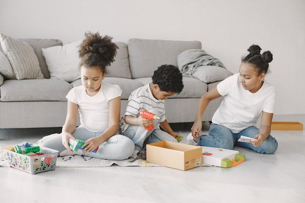 아이들은 바닥에서 게임을합니다. 아프리카 어린이들은 생성자를 구성합니다. 함께 시간을 보내다.