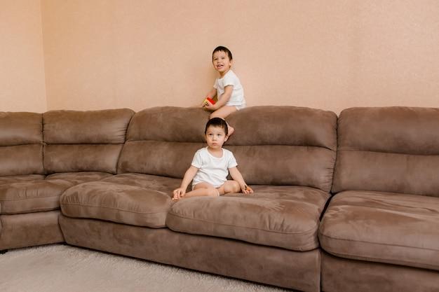 子供たちは自宅の部屋で遊ぶ。 2歳の双子がソファにジャンプ