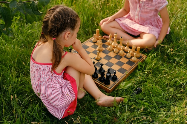 Children play old wooden chess on the lawn on a warm summer day