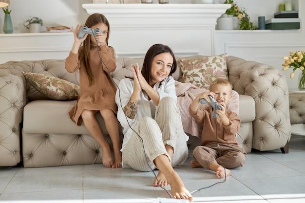 아이들은 어머니와 함께 콘솔에서 게임을합니다. 컴퓨터 게임을 통과하는 기쁨. 콘솔에서 엄마 아들과 딸 전투