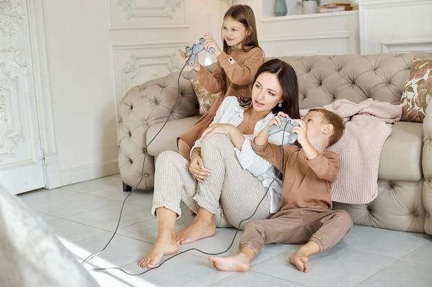 子供たちは母親と一緒にコンソールで遊んでいます。コンピュータゲームを渡すことの喜び。ママの息子と娘がコンソールで戦う