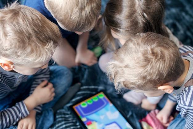 子供たちはタブレットで遊ぶ
