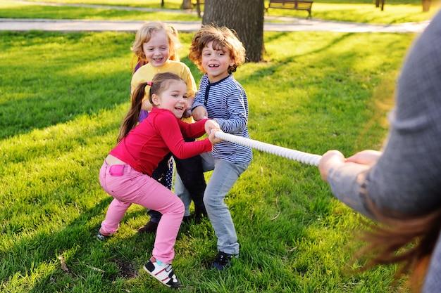 Дети играют в перетягивание каната в парке.
