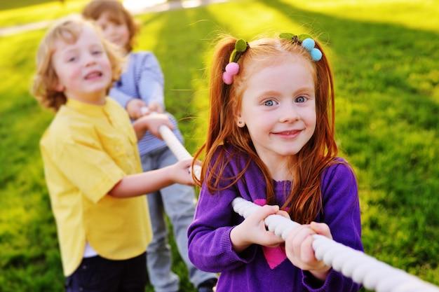 Дети играют в перетягивание каната в парке. Premium Фотографии