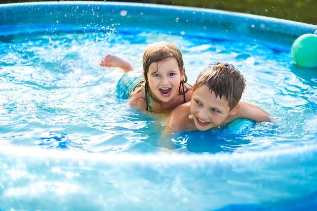 아이들은 더운 여름에 수영장에서 공을 가지고 노는다. 소녀와 소년. 야외 수영장에서 귀여운 소녀