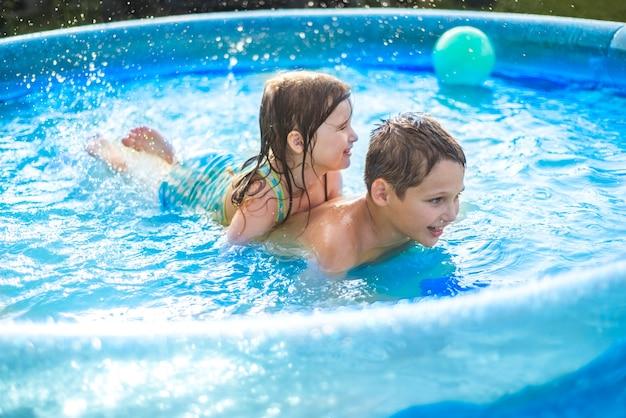 아이들은 더운 여름에 수영장에서 공을 가지고 노는다. 소녀와 소년 야외