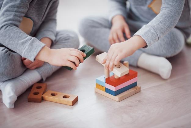 子供たちは子供部屋の床でおもちゃデザイナーと遊ぶ。カラフルなブロックで遊ぶ2人の子供。幼稚園教育ゲーム