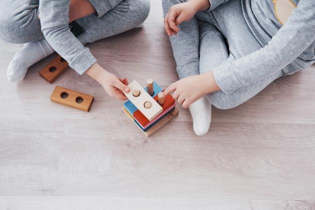子供たちは子供部屋の床でおもちゃのデザイナーと遊んでいます。カラフルなブロックで遊ぶ2人の子供。幼稚園の教育ゲーム。