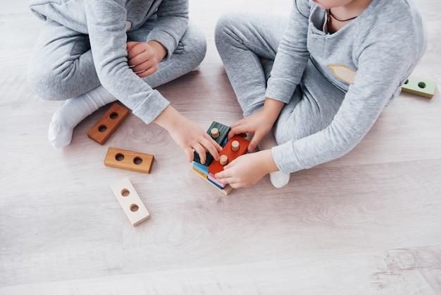 어린이는 어린이 방 바닥에서 장난감 디자이너와 놀고 있습니다. 화려한 블록을 가지고 노는 두 아이. 유치원 교육 게임