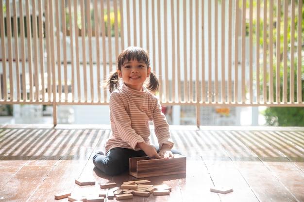 아이들은 어린이 방 바닥에서 장난감 디자이너와 놀고 있습니다.