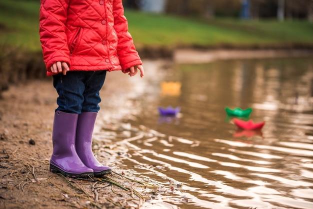 아이들은 강둑에서 보트를 가지고 놀고 있습니다. 화창한 가을. 노란 공원. 석양의 푸른 강