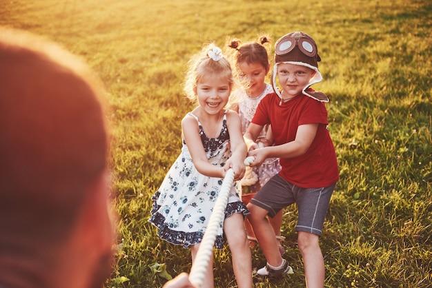 Дети играют с папой в парке. они тянут веревку и весело лежат в солнечный день
