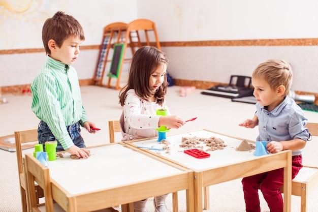 子供たちは幼稚園でキネティックサンドで遊ぶ