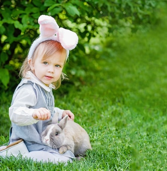 Children play with real rabbit. laughing child at easter egg hunt with pet bunny.