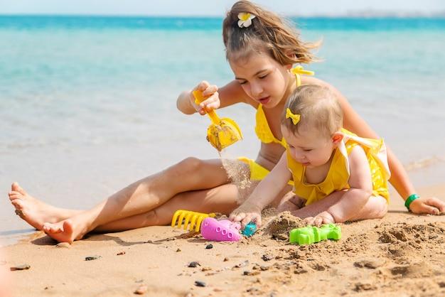 子供たちはビーチで砂で遊ぶ。