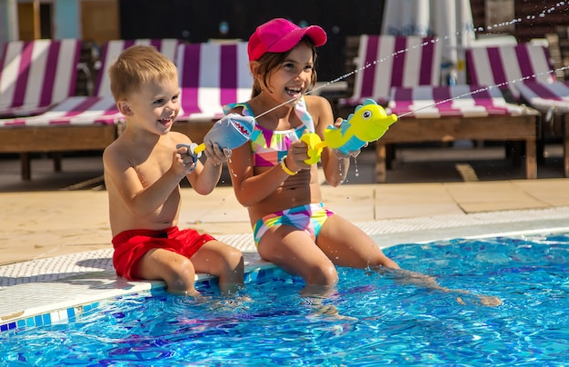 子供たちはプールで水鉄砲で遊んでいます。セレクティブフォーカス。水。