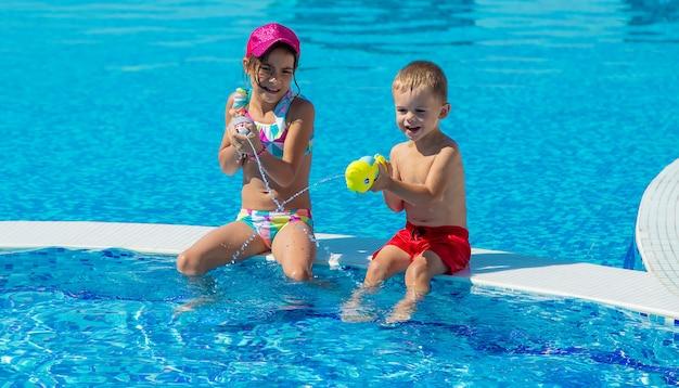 子供たちはプールで水鉄砲で遊んでいます。セレクティブフォーカス。