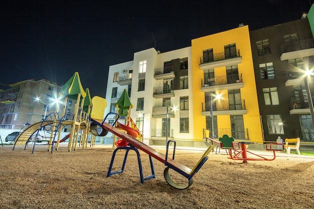 Детская площадка ночью во дворе жилого микрорайона между многоквартирными домами.