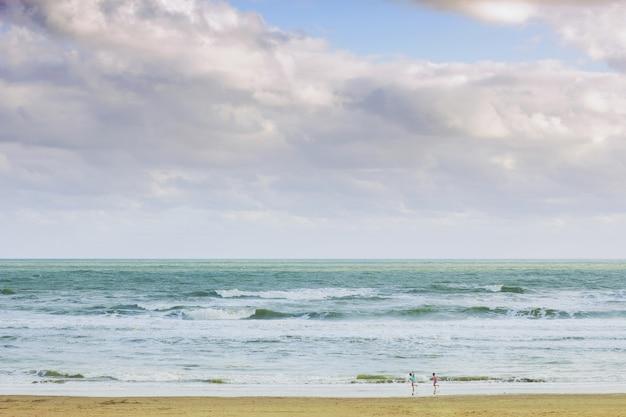 흐린 아침 하늘 아래 해변에서 노는 아이들