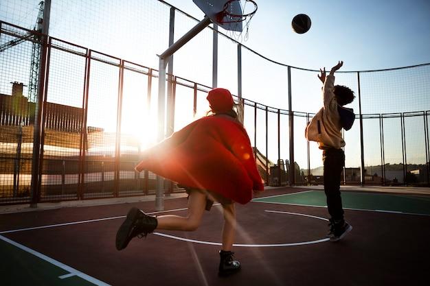 屋外で一緒にバスケットボールをする子供たち