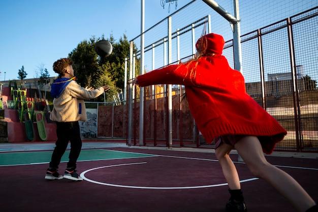 Дети вместе играют в баскетбол на улице