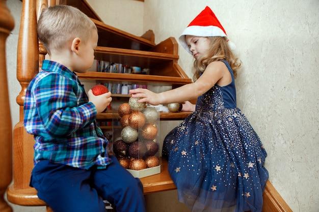 階段に座ってクリスマスのおもちゃを遊んでいる子供たち