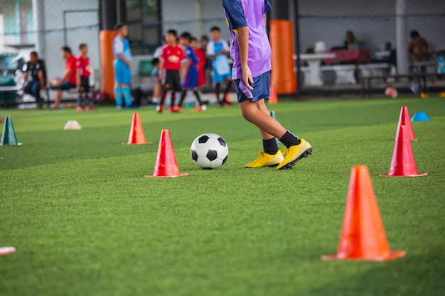 Children playing control soccer ball tactics cone on grass field with for training background training children in soccer