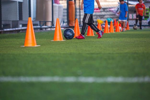 コントロールサッカーボールの戦術を遊んでいる子供たちは、背景を訓練するために芝生のフィールドでコーンサッカーで子供たちを訓練します