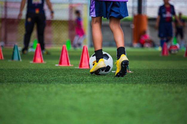 훈련 배경에 대 한 잔디 필드에 제어 축구 공 전술 콘을 재생 하는 어린이 축구에서 훈련 어린이