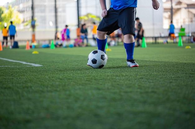 훈련 배경을 위해 잔디 필드에서 제어 축구 공 전술을 재생하는 어린이 축구에서 어린이 훈련