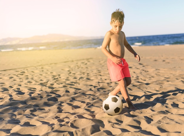 Children playing football on the beach