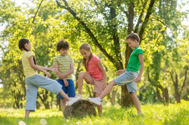 Дети играют на зеленом лугу в парке